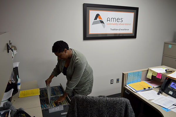 Amber files paperwork for her job with the Ames school district.