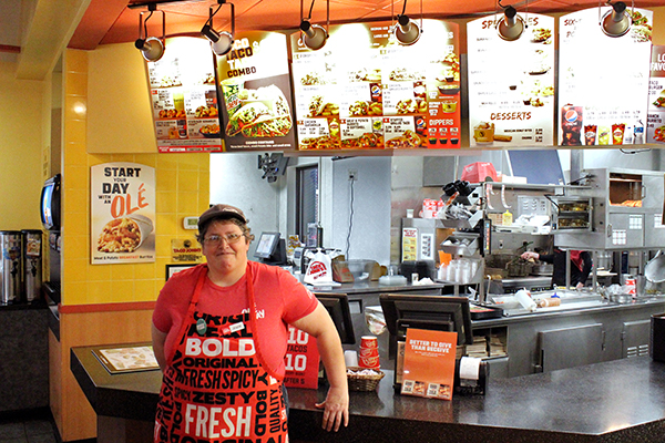 Joyce stands proudly in front of the Taco John's order desk.
