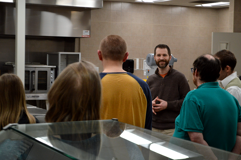 Justin gives a tour of Goodwill of Central Iowa's heaquarters to a group of high schoolers.